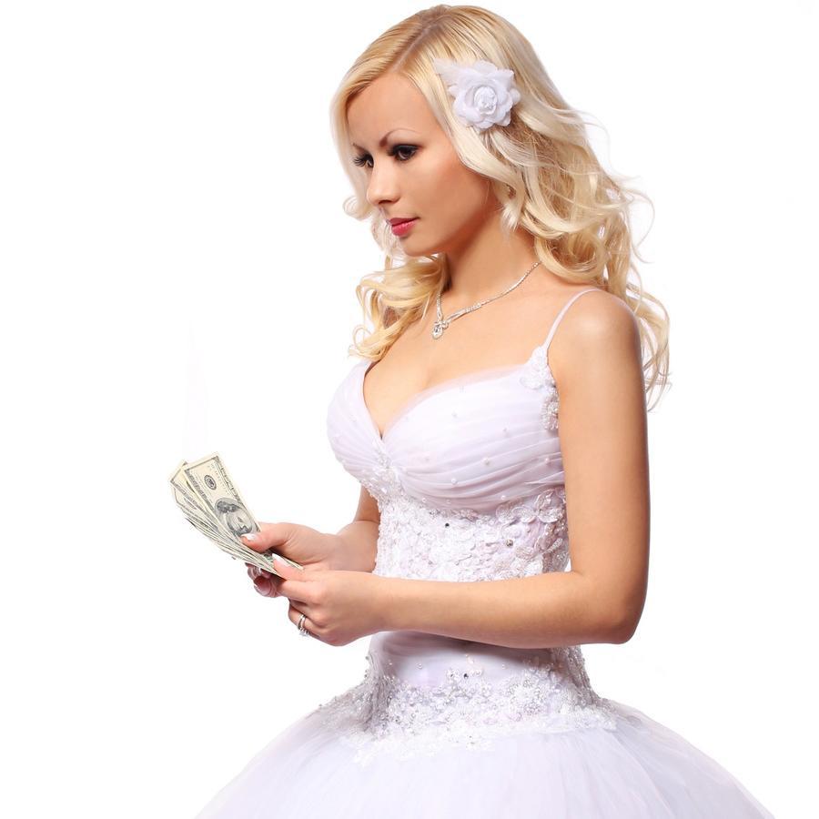 Mujer rubia vestida de novia con billetes en la mano