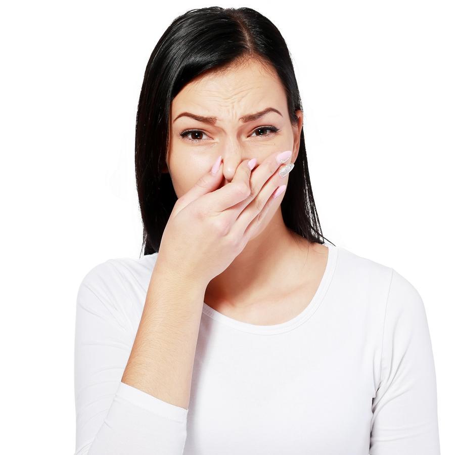 Mujer con blusa blanca y cabello negro tapándose la nariz