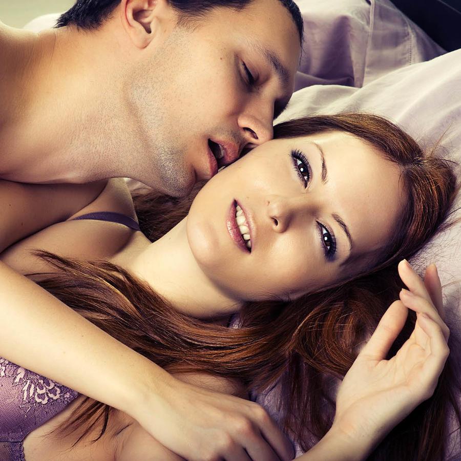 Hombre besando a mujer en la cama