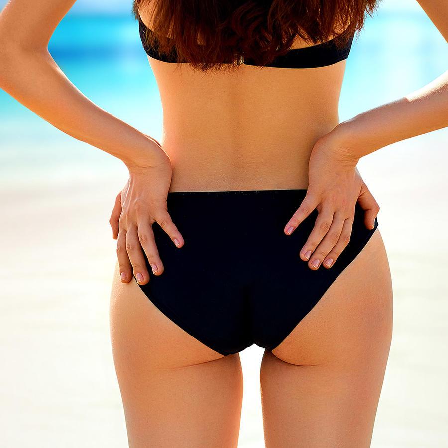 Mujer de espaldas con bikini negra en la playa
