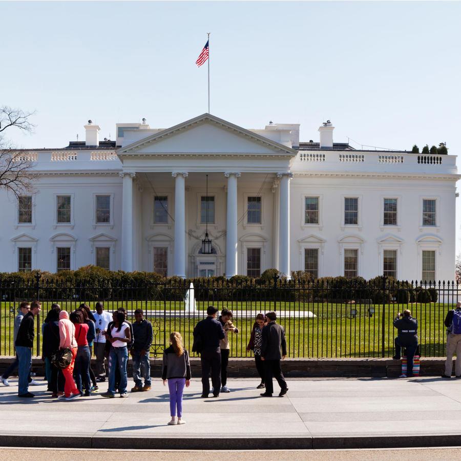Niña de espaldas parada afuera de la Casa Blanca