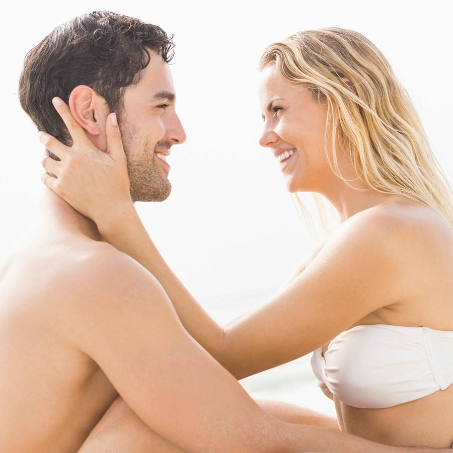 Pareja abrazados sentados en la arena sonriendo