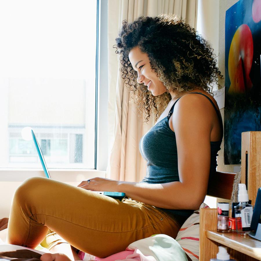 Estudiante universitaria escribe con laptop en la cama