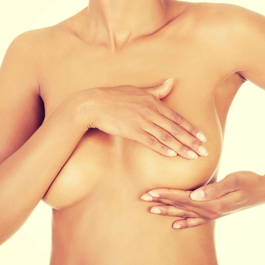 Mujer palpándose en seno izquierdo