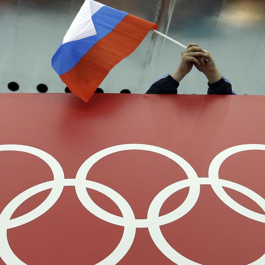 En imagen de archivo del 18 de febrero de 2015, un aficionado ruso al patinaje ondea la bandera de su país sobre los anillos olímpicos de Sochi 2014