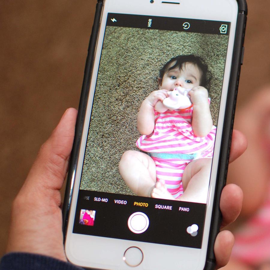 Madre fotografiando a bebé con el celular