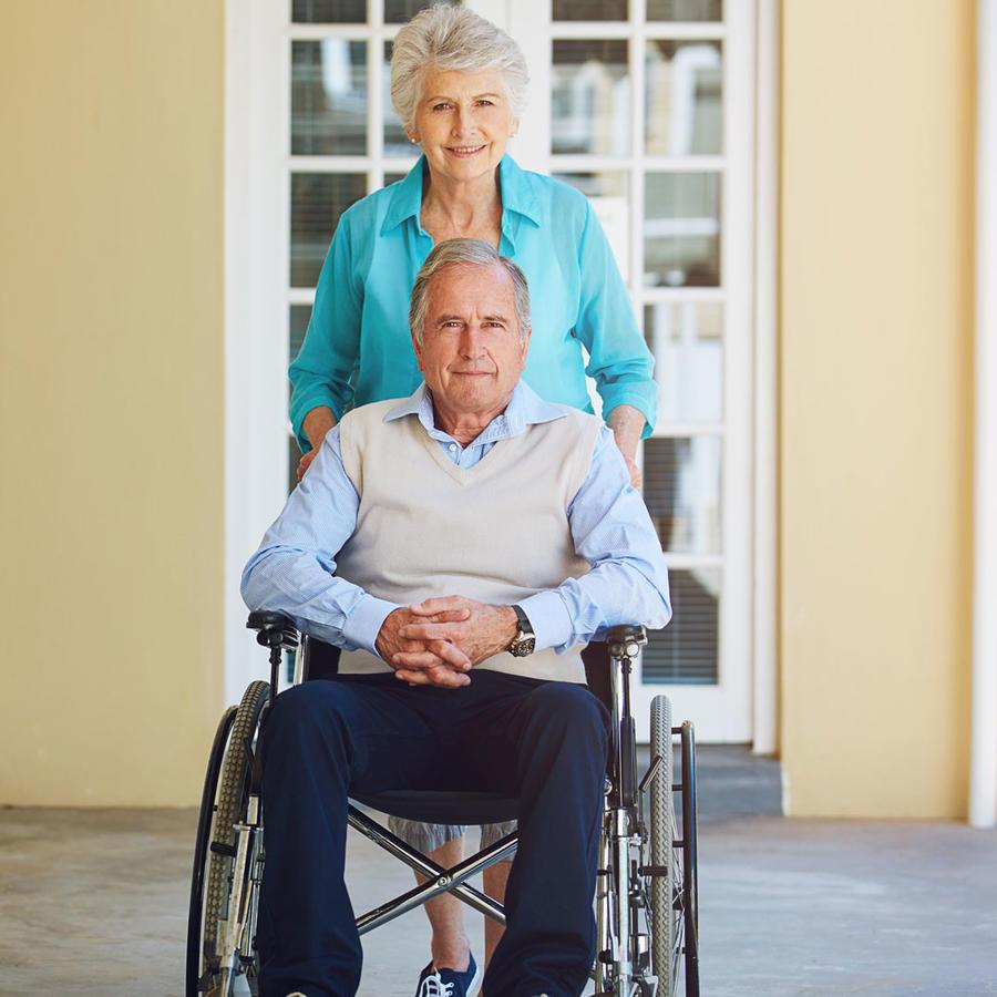 Pareja de jubilados con silla de ruedas