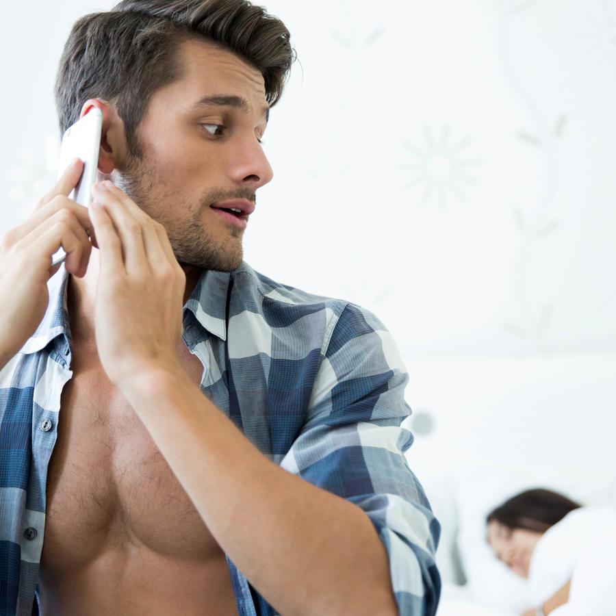 Hombre hablando por teléfono a escondidas de su pareja