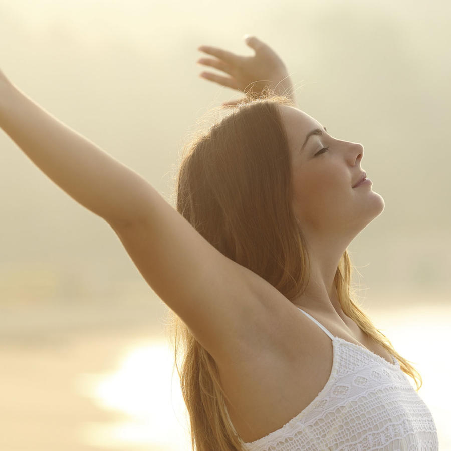 Mujer relajada respirando aire fresco mientras estira los brazos