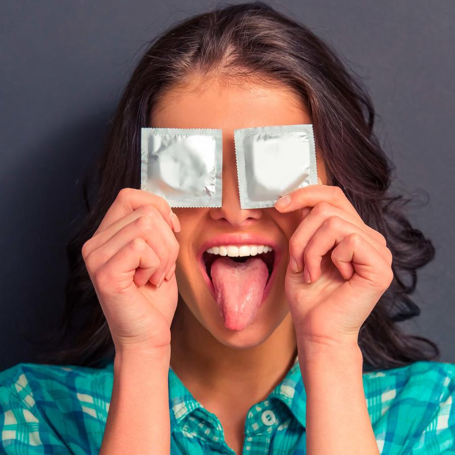 Chica cubriendo sus ojos con condones