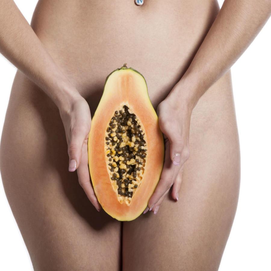 Mujer sosteniendo una papaya sobre su pubis