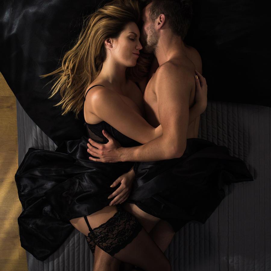 Pareja abrazándose acostada en la cama