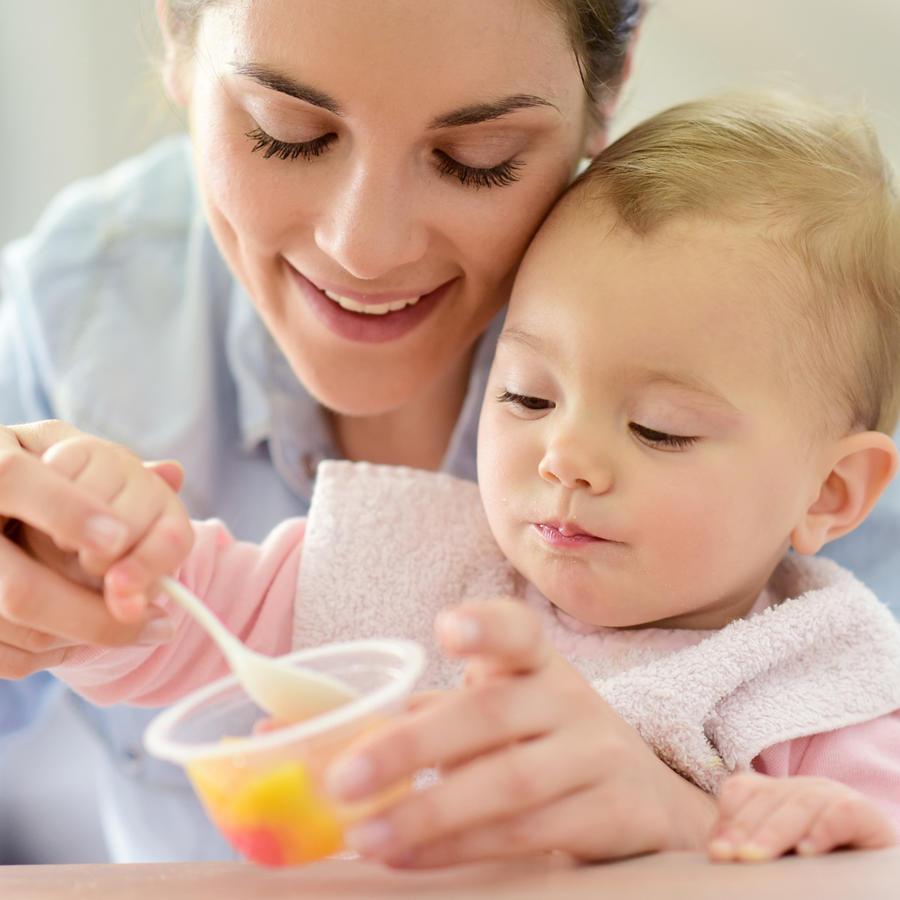Mamá dando de comer a su bebé