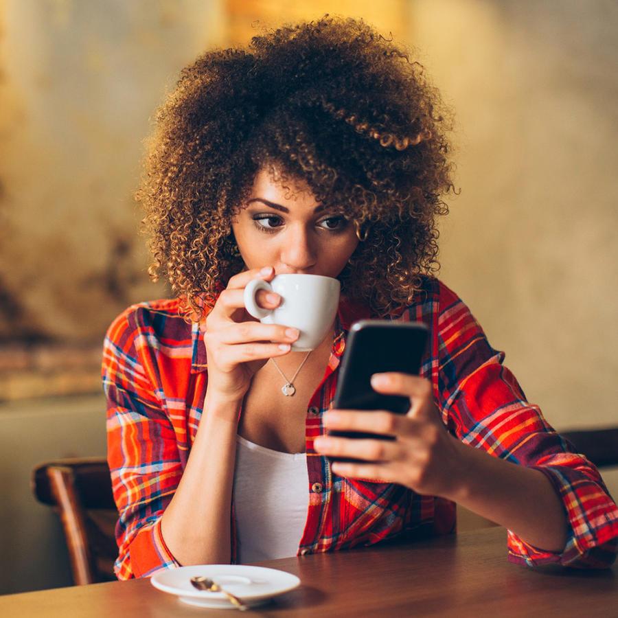Mujer joven checa app y bebe café