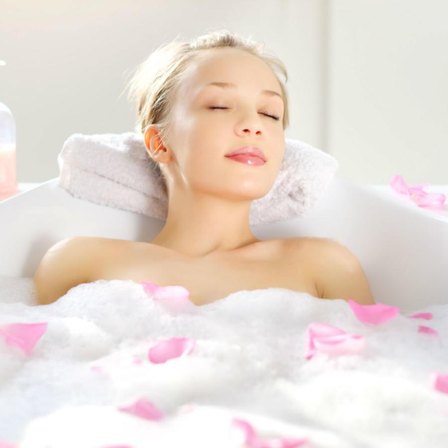 Mujer tomando una ducha caliente con rosas