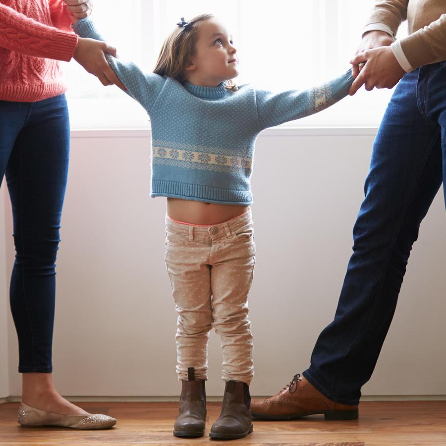 Niña divida entre sus padres