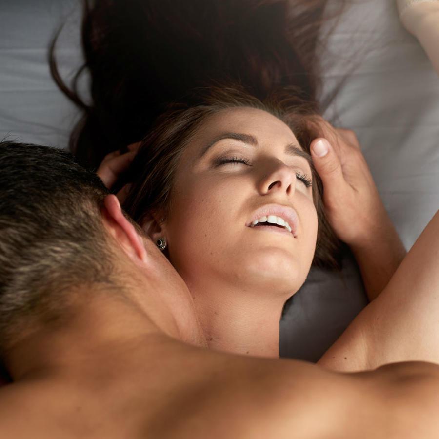 Hombre besando el cuello de una mujer desnuda