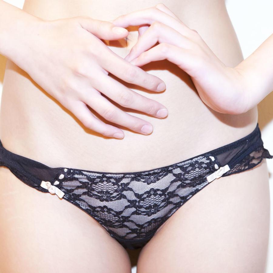 Torso de una mujer usando panty negra con las manos sobre el vientre