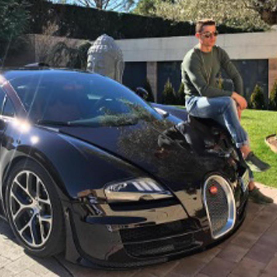 Cristiano Ronaldo posando junto a un lujoso auto deportivo