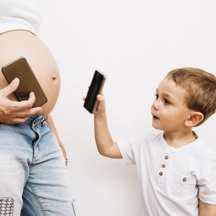 Mamá embarazada usando el celular con su hijo