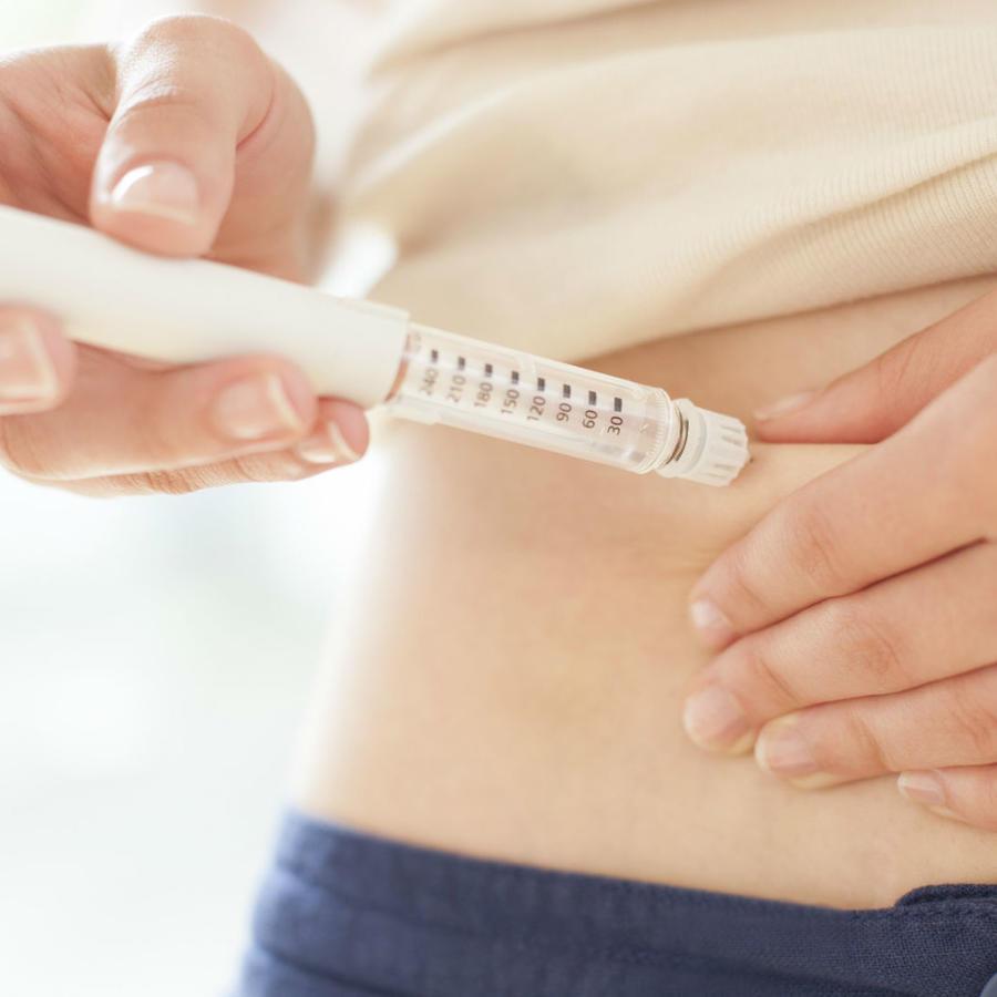 Mujer inyectándose en el abdomen
