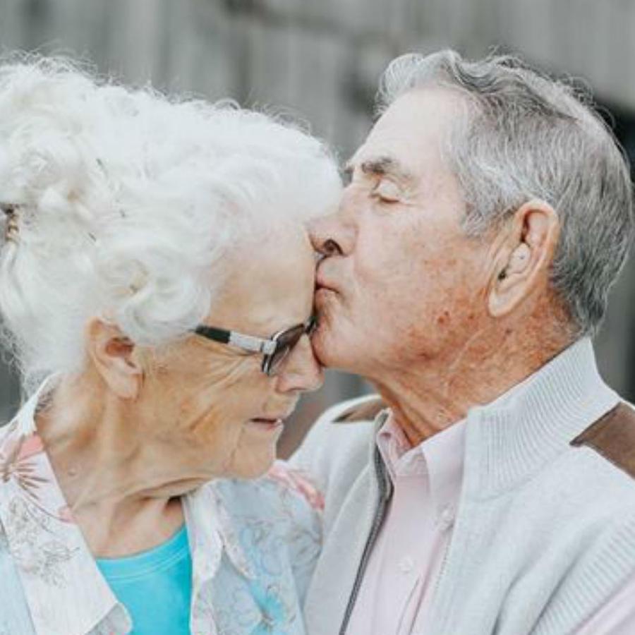 Pareja de abuelitos dándose un beso