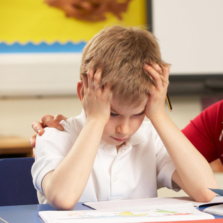 Niño frustrado junto a su maestra