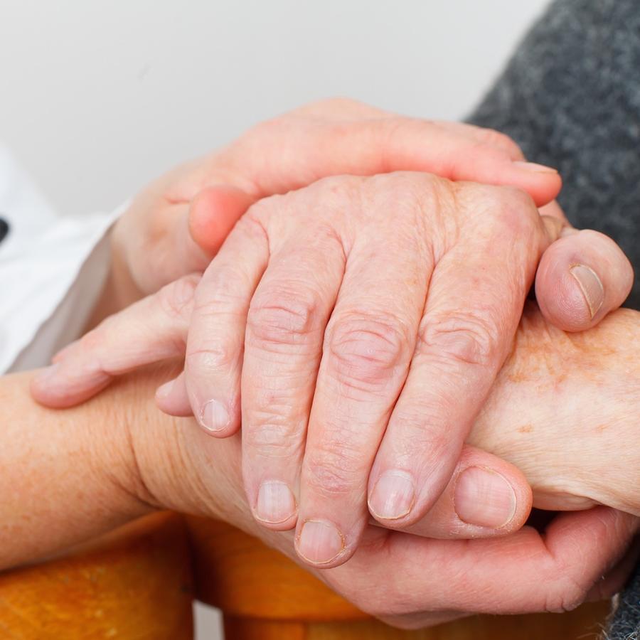 Médico sosteniendo manos de persona mayor
