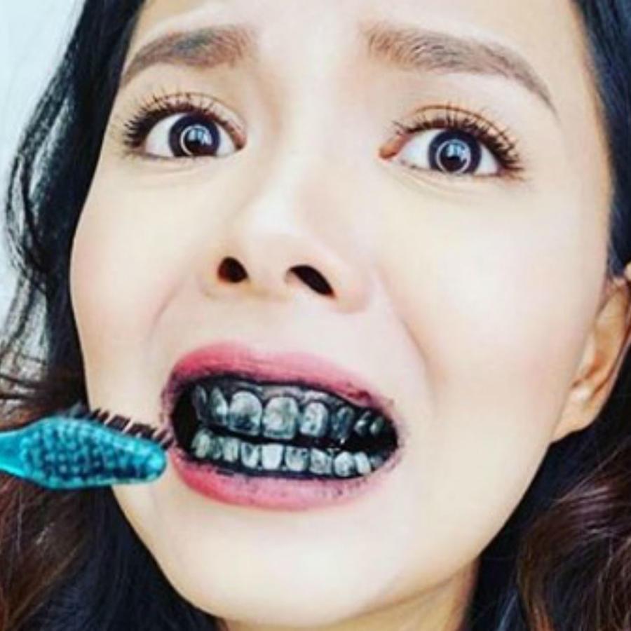 Mujer lavando sus dientes con carbón activado