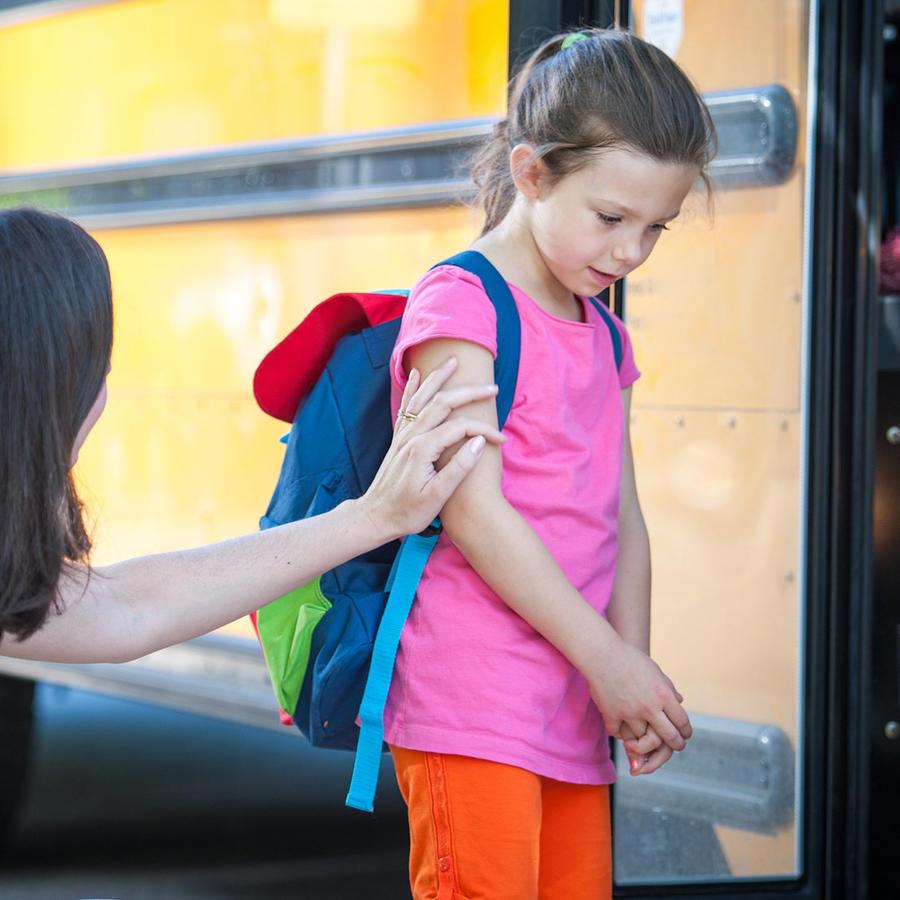 Madre despidiendo a su hija triste frente al autobús escolar