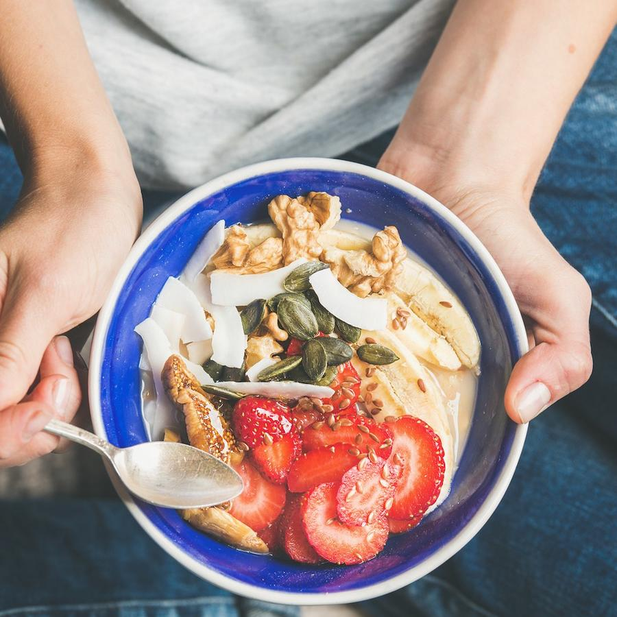 Mujer con bol de fruta, yogur y otros ingredientes