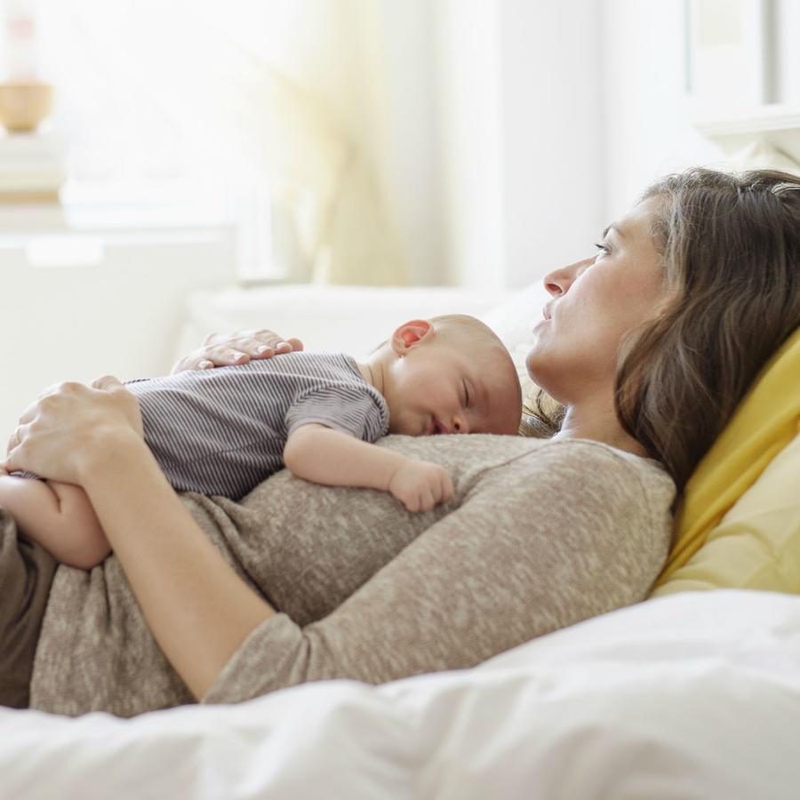 Mamá recostada sosteniendo a su bebé