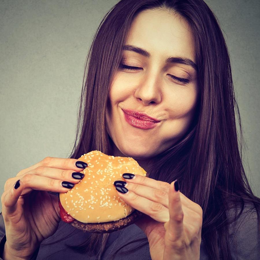 Mujer joven come hamburguesa