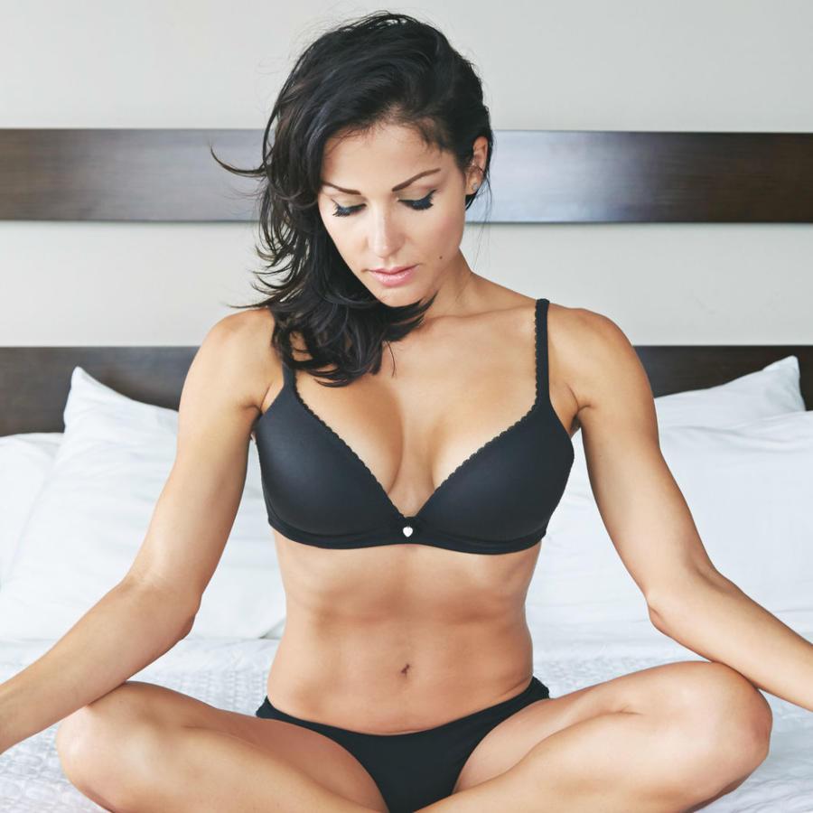 Mujer meditando en la cama en ropa interior