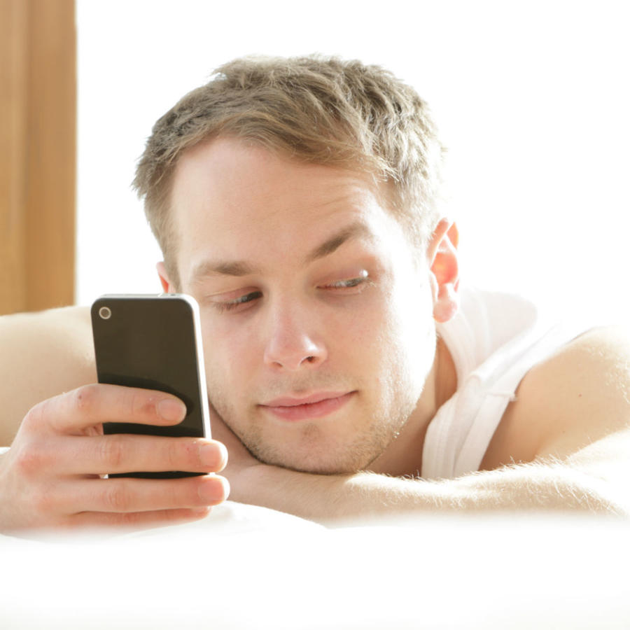Hombre mirando al celular recostado al lado de su novia
