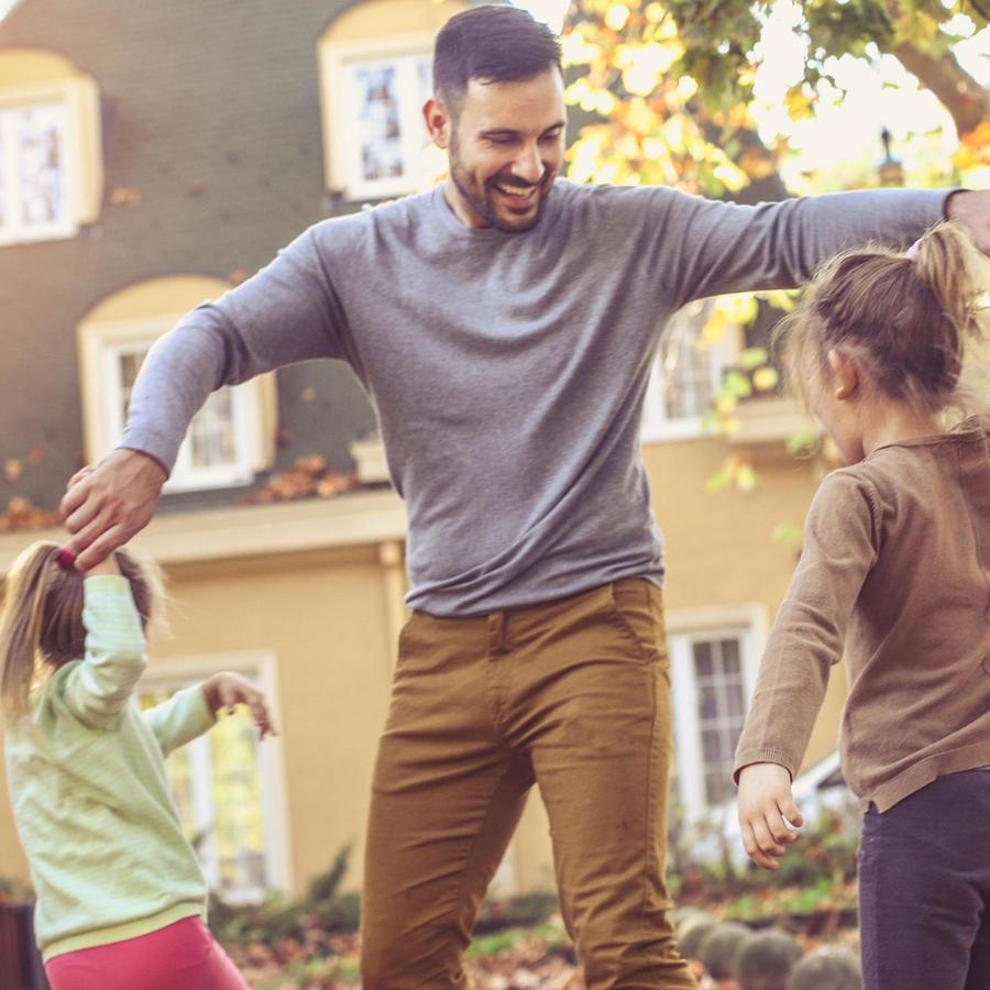 Padre jugando con las hijas en el parque