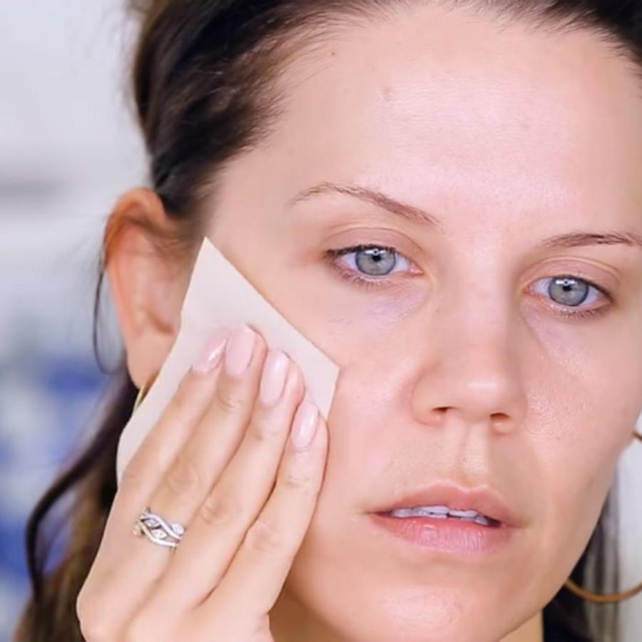 Mujer aplicándose maquillaje de papel
