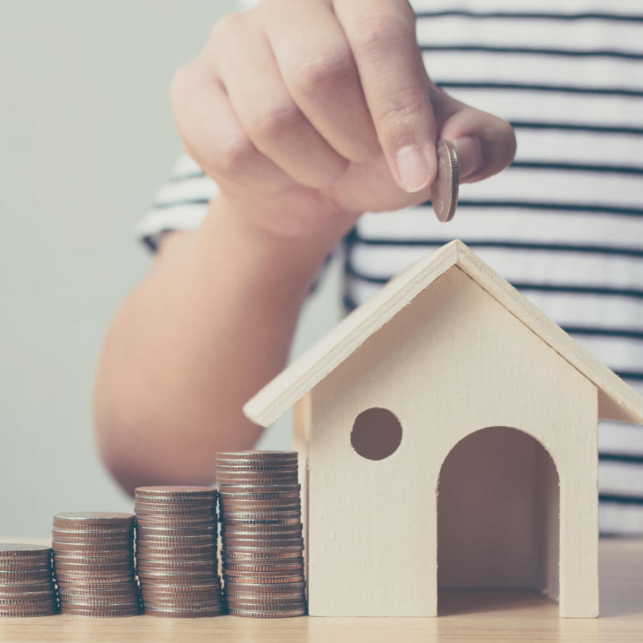 Mujer insertando monedas en casa de madera