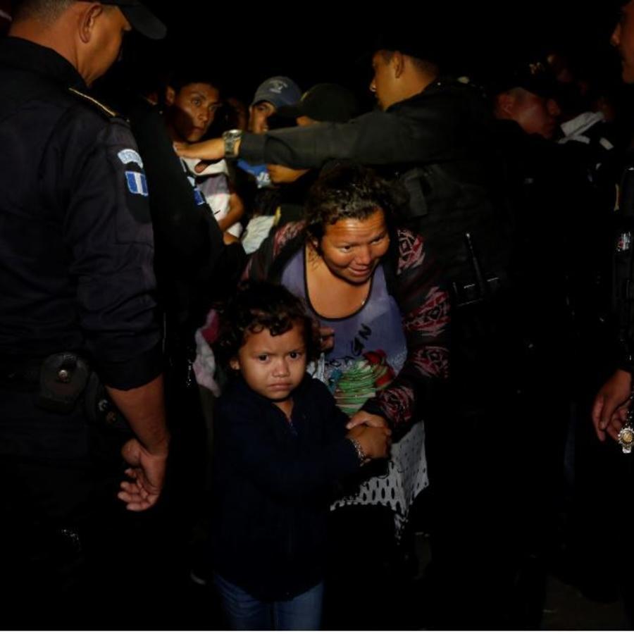 Una familia migrante hondureña atraviesa este martes por la noche un cordón policial en Agua Caliente para entrar en Guatemala.