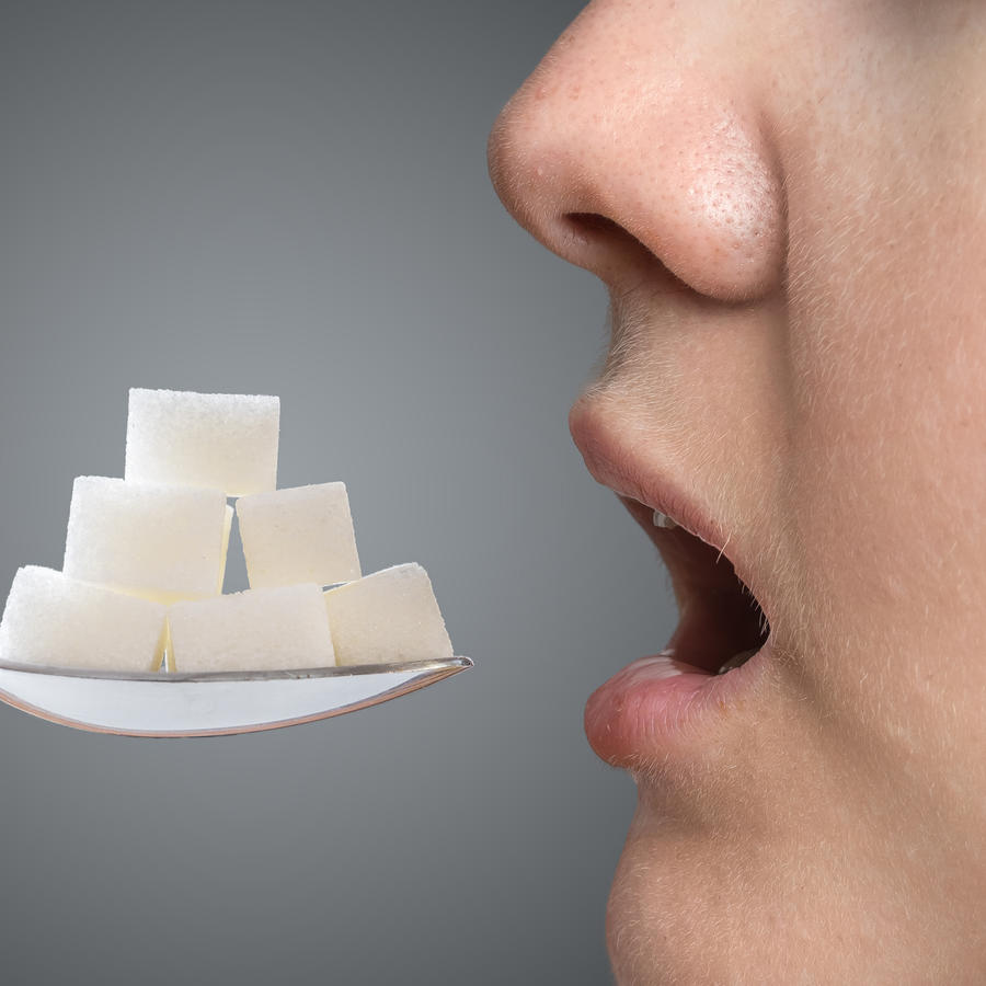 Woman addicted on sugar is eating spoon full of sugar blocks. Unhealthy eating concept.