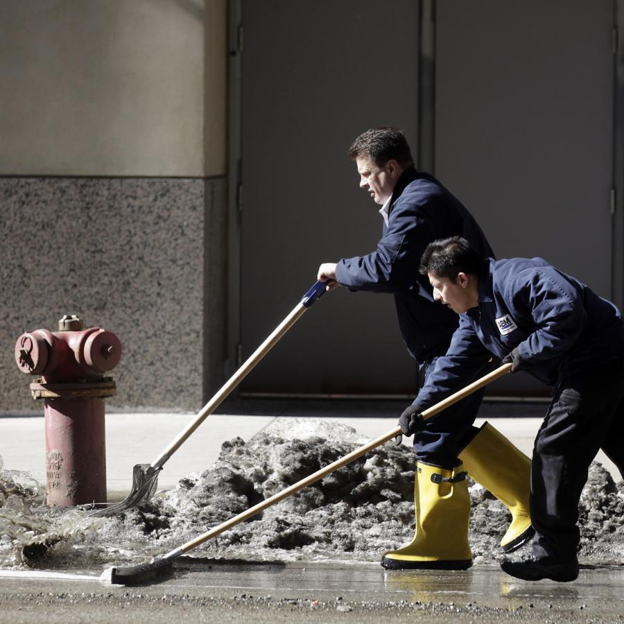 dos trabajadores removiendo nieve durante un deshielo