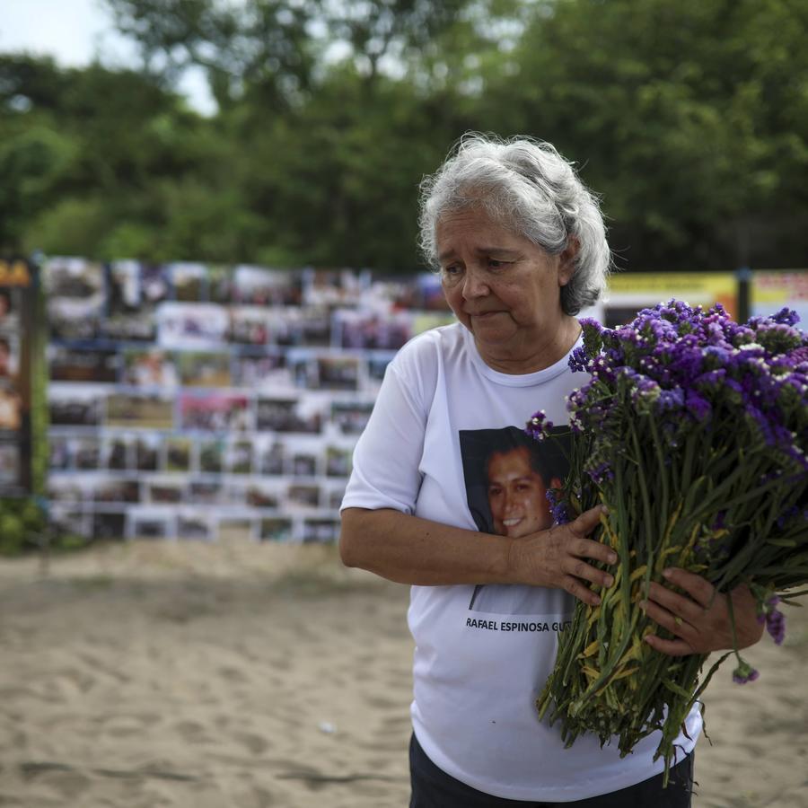 Una mujer lleva flores al lugar donde 300 restos humanos fueron hallados en una fosa clandestina