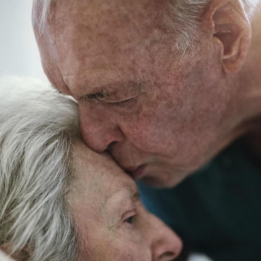 Anciano besando en la frente a su esposa