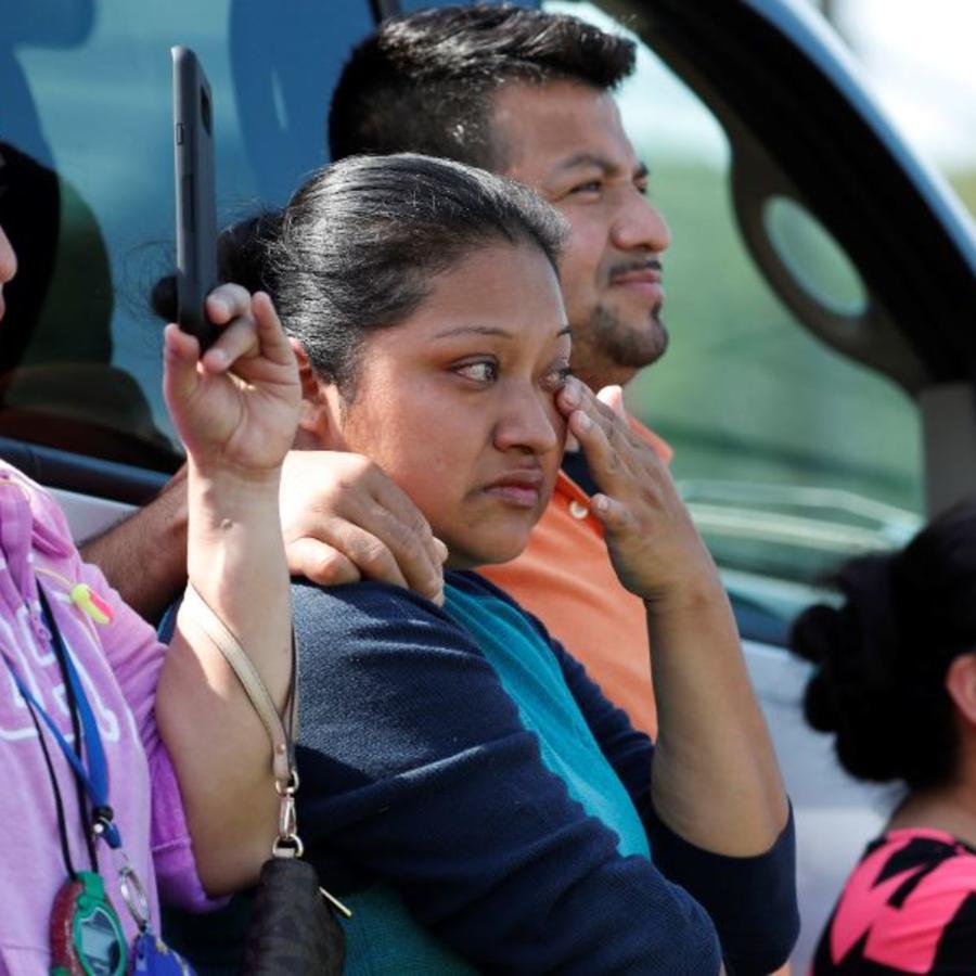 Amigos, compañeros de trabajo y familiares observan cómo los funcionarios de inmigración de EE. UU. intervienen en la planta de Koch Foods Inc. en Morton, Misisipi, este miércoles.