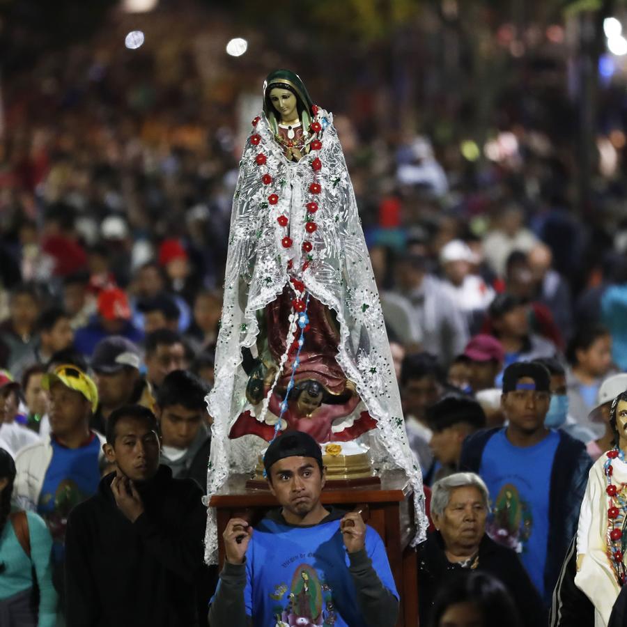 Peregrino carga un busto de la Virgen de Guadalupe