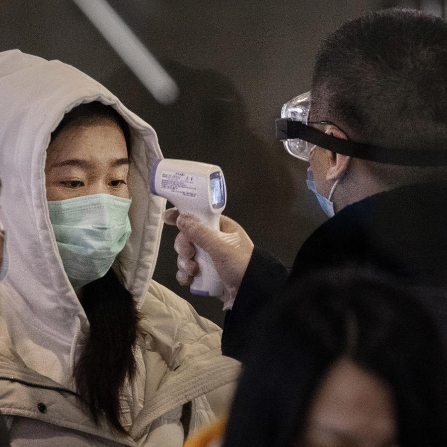 Ciudadanos chinos son examinados en una estación de tren
