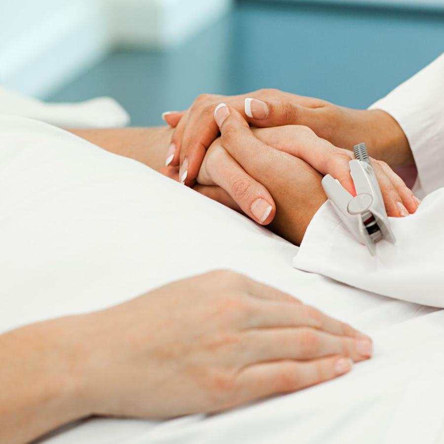Doctora sosteniendo la mano de una paciente