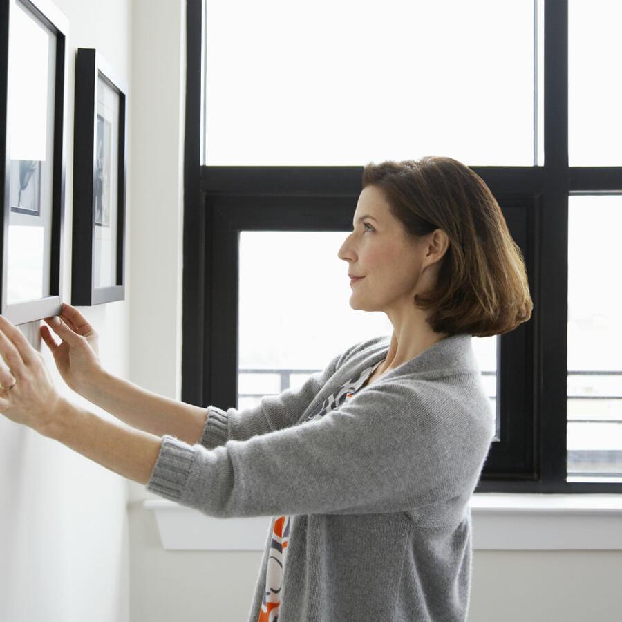 Mujer arreglando un cuadro