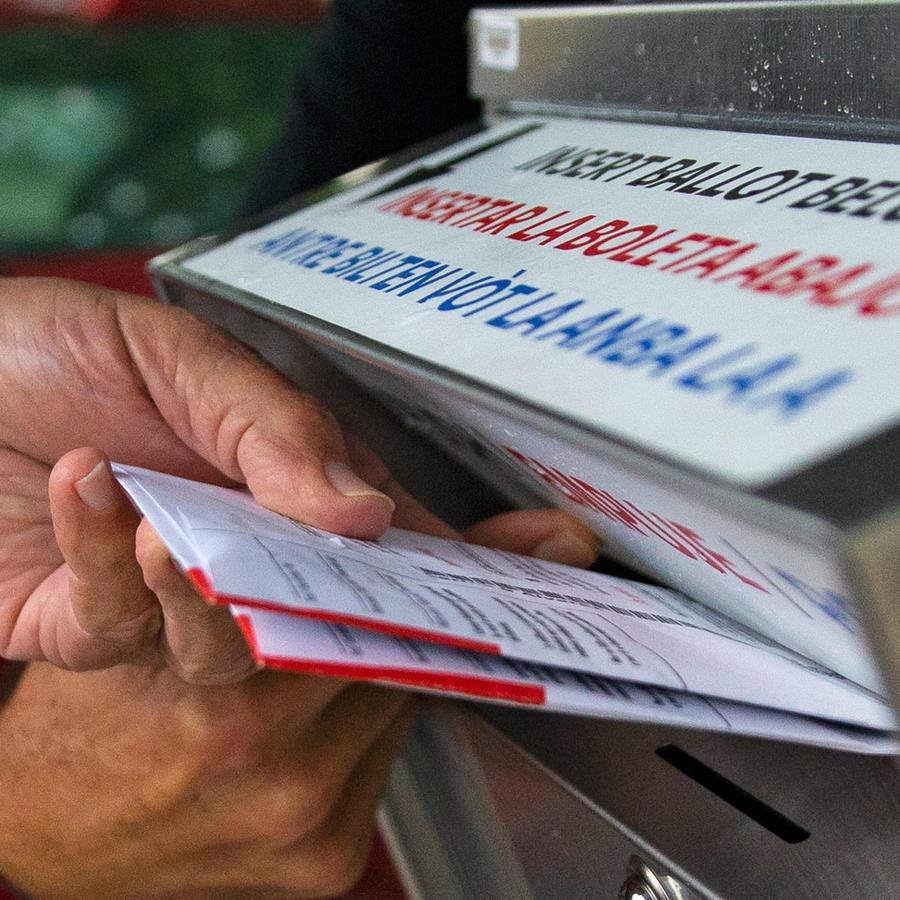 Una persona deposita su boleta en un buzón en Florida.