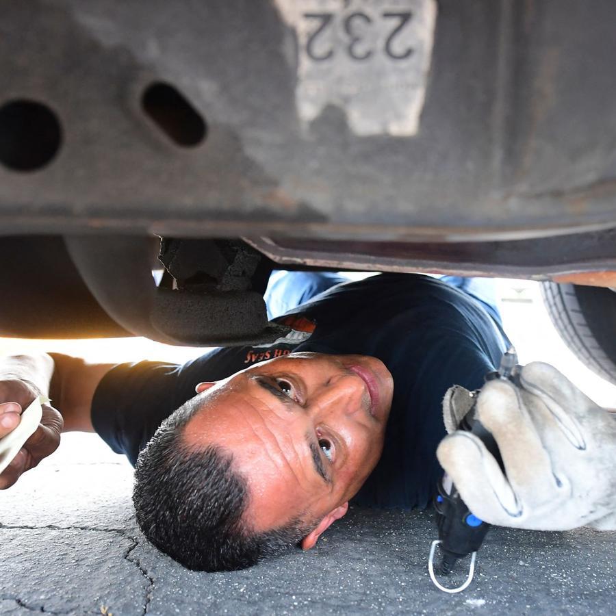 El diputado Jaime Moran del Departamento del Sheriff del condado de Los Ángeles graba el convertidor catalítico de un vehículo con un número rastreable el 14 de julio de 2021.